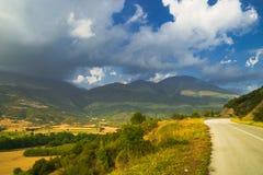 campos amarillos en las montañas cerca del camino con el cielo nublado Fotos de archivo