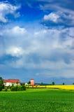 Campos cultivados con el molino y el cielo nublado Fotos de archivo libres de regalías