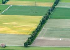 Campos de cultivo y filas de árboles con un avión del plumero de la cosecha visto desde arriba imagen de archivo