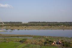 Campos de granja verdes cerca del río Yamuna y de hogares temporales de campesinos Puente de la firma Delhi la India imagen de archivo libre de regalías