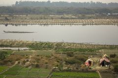 Campos de granja verdes en los bancos del río de Yamuna y de los hogares temporales de campesinos Puente de la firma Delhi la Ind imagenes de archivo