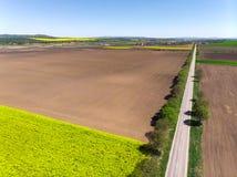 Campos de la primavera y pistas del tractor Imagen de archivo libre de regalías