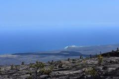 Campos de lava en la isla grande en Hawaii con el Océano Pacífico en el fondo foto de archivo