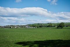 Campos do Ayrshire que olham sobre à cidade dos empréstimos e ao bosque alto em Escócia imagem de stock