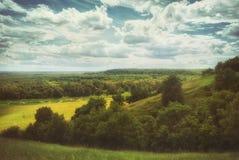 Campos e prados em um vale montanhoso sob um céu nebuloso do verão foto de stock royalty free