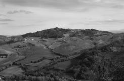 Campos e vindo raramente através das casas no terreno montanhoso fotos de stock
