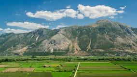Campos verdes debajo de las montañas Foto de archivo libre de regalías