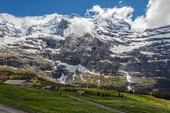 Campos verdes e cidade turística impressionante famosa com os penhascos altos no fundo, Suíça, Europa Fotos de Stock