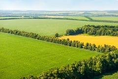 Campos verdes y amarillos sobre la visión aérea Imagen de archivo libre de regalías
