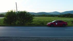Campos verdes y una carretera con el coche parqueado, veiw del lado tiro El camino a lo largo de campos y de bosques en el cielo  almacen de metraje de vídeo