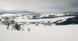 Campos y montañas Nevado, y una pequeña ciudad rural Imagen de archivo