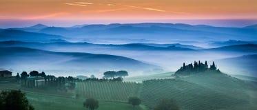 Campos y prados verdes hermosos en la puesta del sol en Toscana Fotos de archivo
