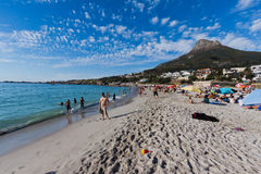 Camps Bay beach and Lions Head Mountain. Tourists enjoying the white sand of Camps Bay beach with Lions Head Mountain in the back Royalty Free Stock Photo