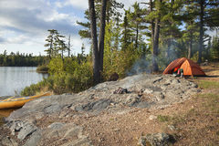 Campsite on Boundary Waters lake in northern Minnesota. Campsite with orange tent and canoe on a lake in the Boundary Waters Canoe Area Wilderness of Minnesota stock photography
