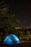 Campsite with illuminated tent and stars in dark sky. Royalty Free Stock Photography