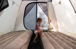 At the campsite, a little girl in a tent jumps on mattresses. The little girl a small tent opening lying back to nature to make the familiar In the midst of the royalty free stock image