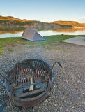 Campsite on Mountain Lake at Sunset. A campsite on a mountain lake with a tent set up by the shore as the sun sets Royalty Free Stock Photos