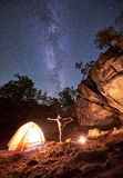 Campsite at night. Athletic slim girl doing stretching gymnastic exercises at small tourist tent. Campsite at night amid huge steep rock formations. Athletic royalty free stock image