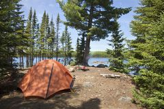 Campsite with orange tent and fire on a northern Minnesota lake. During summer stock photo