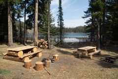 Campsite with picnic tables. A campsite with picnic tables and supplies for campfire near a lake in Canada Stock Photography
