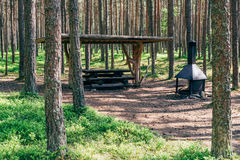 Campsite in summer forest. Camping place with wooden table and grill in summer forest. Well organized campsite stock images