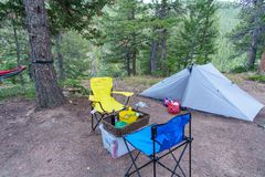 Campsite with tent, hammock, chairs, and dinner all ready stock image