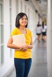 Campus asiático lindo sonriente del libro de la muchacha Foto de archivo libre de regalías