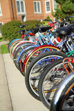 Campus bicycles. Bicycles stored on a bike rack outside a college dorm building. Image of pollution free way of transportation stock photos
