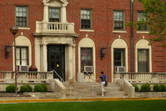 Campus Living Quarters. Female student climbing the front steps of a college dormitory Stock Image