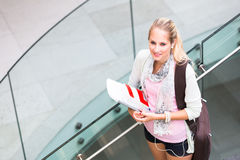 On campus - pretty, female student with books and laptop Royalty Free Stock Photography