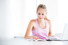 On campus - pretty, female student with books and laptop working Stock Photos