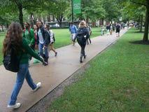 Campus universitário: Estudantes que andam entre a classe imagens de stock