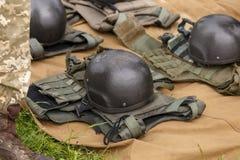 Camufle las chaquetas y los cascos de fuego antiaéreo del combate alineados en la tierra fotos de archivo