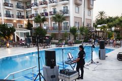 Unknown musician performs in front of hotel guests. CAMYUVA, KEMER, TURKEY - JULY 14, 2015: Unknown musician performs in front of hotel guests stock photography