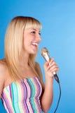 Canção fêmea nova bonito do canto, isolada sobre o azul Fotografia de Stock