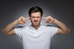 Can� услышит его больше. Портрет молодых человеков закрывая его уши b Стоковые Изображения RF