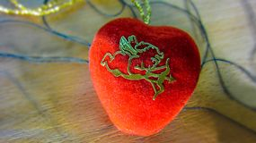 The bright red heart with the symbol of the Amur lying on a wooden background with a confusing black thread. Can be used for the concept of romance, love royalty free stock image