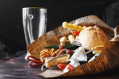 A can of beer with a snack on a wooden dark background with an empty beer glass. Gift bouquet to a man Stock Photo