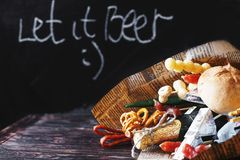 A can of beer with a snack on a wooden dark background . gift bouquet to a man. Men`s holiday gift Stock Photos