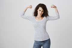 She can bit your boyfriend. Portrait of good-looking curly-haired woman with confident attitude showing muscles with. Raised hands, smiling, expressing girl stock photo