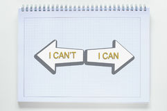 Can or cannot. Can and cannot with arrow on spiral notebook with grid paper on white background Royalty Free Stock Photos
