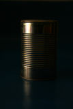 Can in the Dark. A lone can without a label stands on a dark shelf Royalty Free Stock Photo