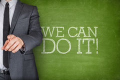 We can do it on blackboard with businessman Stock Photography