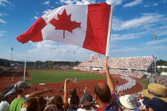 CAN flag crowd 01. A fan waves a Canadian flag at the Commonwealth Games Stock Photos