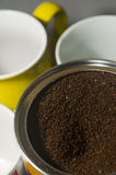 Can of ground coffee beans with mugs Stock Images