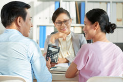 We can have a good loan. Vietnamese men showing loan amount on calculator screen to his wife Royalty Free Stock Photos