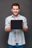 This can help you!. Cheerful young man shoving his digital tablet with copy space and looking at camera with smile while standing against grey background Stock Photo