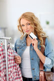 Can I afford it?. Woman in clothing store holding credit card Stock Photo