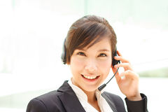 Can I help you?. Attractive cheerful asian operator ready to help you Royalty Free Stock Images