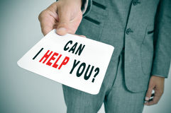 Can I help you?. Man wearing a suit showing a signboard with the sentence Can I help you? written in it Royalty Free Stock Photography